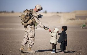 The soldier gives an apple to kids. The Act of Kindness.