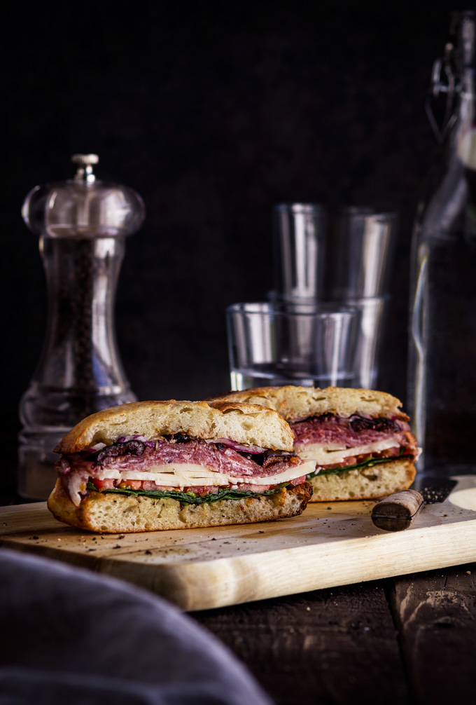 This easy to make muffuletta sandwich recipe is a must for the Italian antipasto lovers. It is made of muffuletta bread infused with fragrant olive oil dressing, layers of gorgeous Italian cold cuts and cheeses. Make this Italian sandwich a day ahead to save some time because this New Orleans pride gets better as it sits. #muffuletta #sandwich #italiansandwich