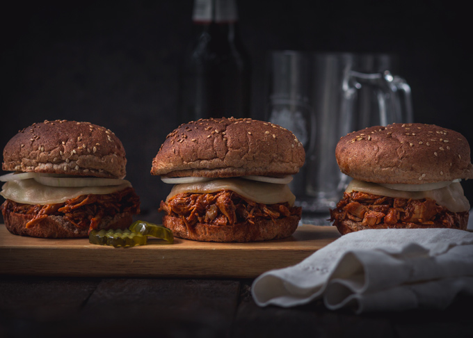 Amazing bbq chicken sliders recipe. These pulled chicken sliders consist of two parts: the homemade BBQ sauce and bbq shredded chicken. Both recipes included. Soft slightly toasted whole wheat buns. Creamy, chewy cheese. And a thinly sliced onion. All of these layers combined create the best chicken sliders. Instant pot chicken sliders are a delicious and easy way to feed a crowd! Or a great finger food dinner to enjoy with friends and family. #bbq #chicken #sliders #burger