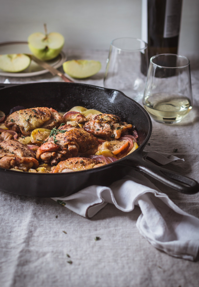 This easy one-pan apple chicken thighs is a healthy, comforting and delicious dinner to make any time of the year, especially in fall. All you need is one skillet, fresh produce, flavorful wine, and thyme. And in about 30 minutes you a have a simple yet delightful apple chicken dinner. Perfect for busy weeknight meals. Serve it with rice or your favorite grains. #chicken #dinner #chickenrecipe #apples #healthy