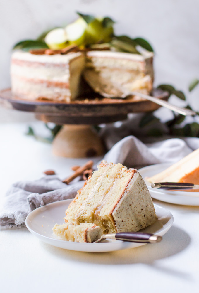 This lighter apple layer cake with whiskey almond frosting is a true fall celebration. It is made with layers of light and airy genoise (sponge) cake with light whiskey scented cream in between and an aromatic apple filling! This can be a Thanksgiving apple layer cake, a special occasion layer cake or a cake to celebrate the most flavorful season – autumn. One thing for sure – this apple and almond layer cake steals the show! Truly the best apple layer cake! #cake #apples #apple #dessert #layercake